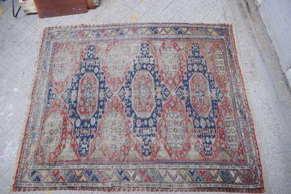 Tapis Kilim fond rouge à décor géométrique bleu. H.: 240 cm - L.: 166 cm Usures...