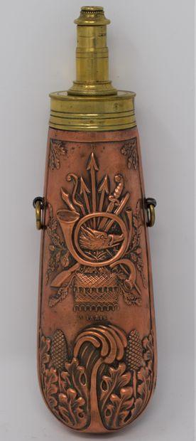 Poire à poudre droite en laiton et cuivre repoussé à décor cygénétique, signé B...