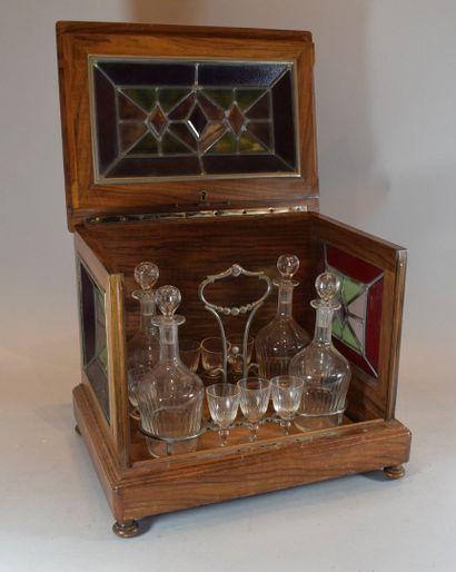 Cave à liqueur en bois naturel agrémenté de verres colorés comprenant quatre carafes...