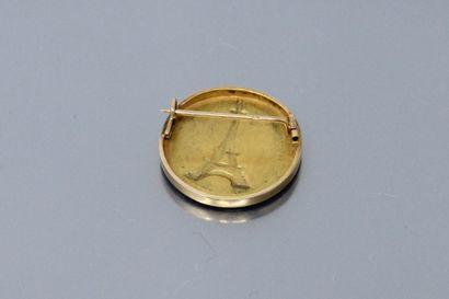 Broche ronde en or jaune 18K (750), présentant une gravure de la tour Eiffel, devant...