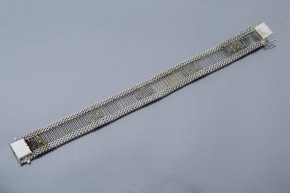Bracelet en or gris 18K (750) ajouré à motifs de fleurs, entre deux lignes de maille...