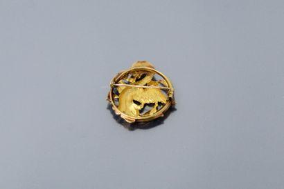 Broche ronde ajourée en or jaune 18K (750) à décor de chimère phytomorphe tenant...