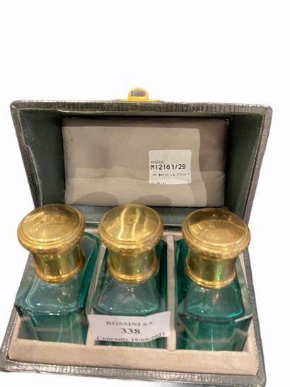 Un écrin de trois flacons à parfums en verre...