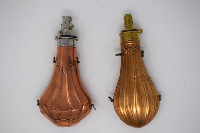 Deux poires à poudre en cuivre repoussé et distributeur en laiton :  - décor d'une...
