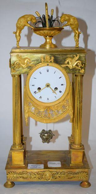 Pendule portique en bronze doré surmonté...