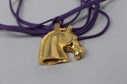 HERMES Paris  Pendentif en métal doré, figurant une tête de cheval. Porte l'inscription...