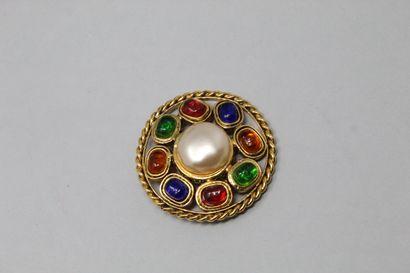 CHANEL Broche ronde en métal doré ajourée, ornée d'une perle fantaisie en son centre...