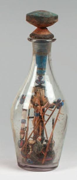 Crucifix en bois polychrome dans une bouteille...