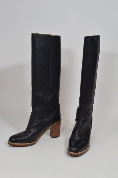 Paire de bottes à talons en cuir noir.  Signées...
