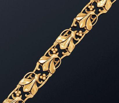 Bracelet ruban souple en or jaune 18K (750) articulé de motifs ciselés au repercé...