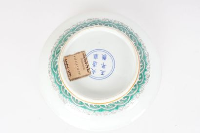 ASSIETTE  Une assette en porcelaine de la Famille Rose représentant une scène entre...