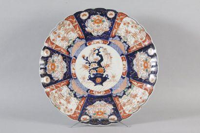 Japon Plat rond en porcelaine à bord lobé à décor bleu, rouge et or dit Imari d'une...
