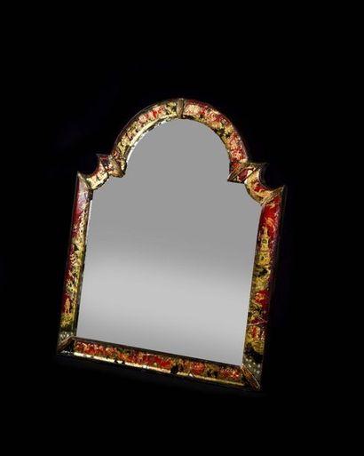 Miroir en verre églomisé, de forme contournée,...