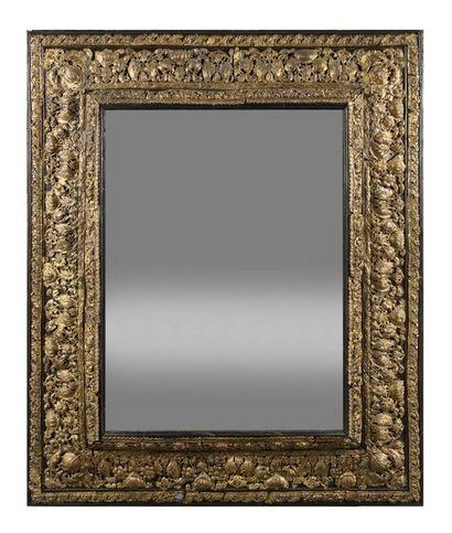 Miroir en bois noirci et cuivre repoussé...