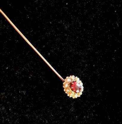 EPINGLE A CRAVATE en or jaune ornée d'un rubis entouré de demi perles fines. Poids...