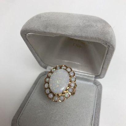 BAGUE en or jaune sertie d'une opale dans un entourage de petites opales. Poids...