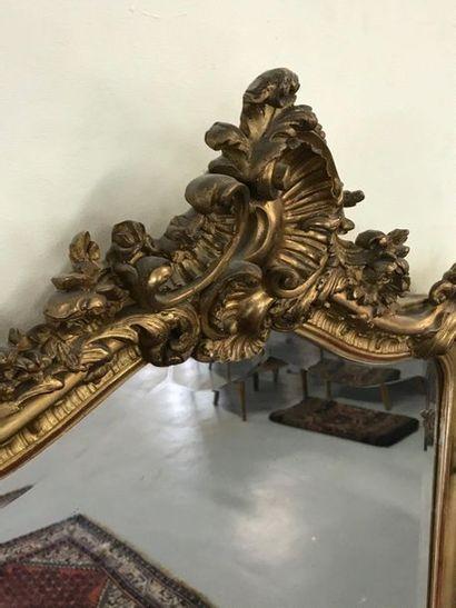 MIROIR  De style Louis XV en bois et stuc doré à décor surmontée d'une coquille....