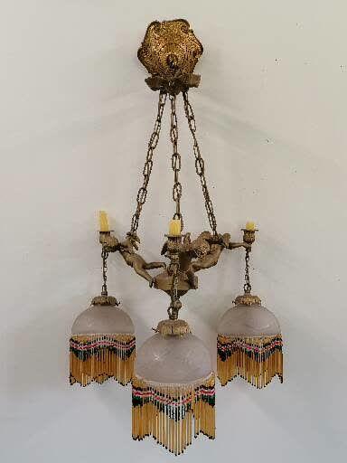 LUSTRE  En bronze à décors de trois angelots...