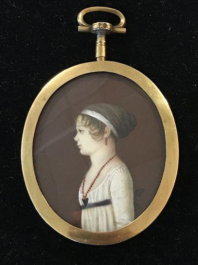 PORTRAIT MINIATURE  en médaillon d'une jeune femme de profil portant un collier...