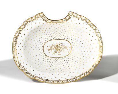 SEVRES Plat à barbe ovale en porcelaine dure à décor en or au centre de bouquets...