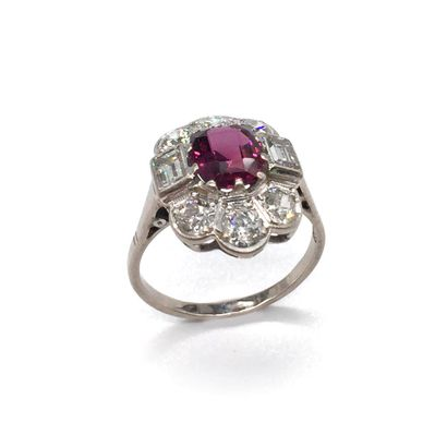 RING holding a ruby in a circle of six old cut diamonds and two rectangular diamonds....