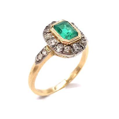 BAGUE présentant une émeraude d'environ 0.50 carat dans un entourage de diamants...