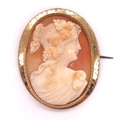 BROCHE retenant un camée présentant une femme de profil, dans un entourage en or...