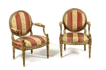 PAIRE DE FAUTEUILS A DOSSIER PLAT en médaillon en bois sculpté et doré, les accotoirs...