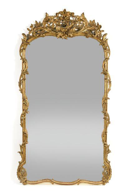 GRAND MIROIR en bois doré de style Louis XV, le cadre mouvementé en bois moulé,...