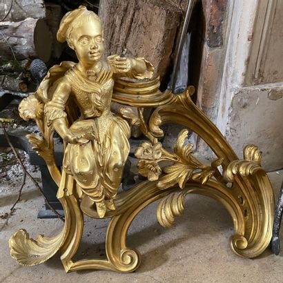 """A PAIR OF CHENETS called """" à la tasse de chocolat """" in chased and gilded bronze..."""