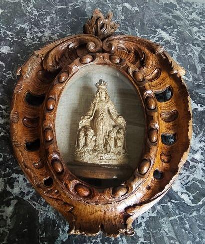 MÉDAILLON en chêne sculpté et ajouré à décor...