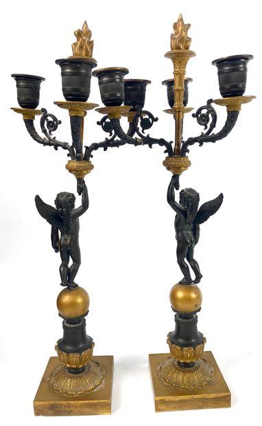 PAIRE DE CANDELABRES en bronze doré et patiné à décor d'angelots retenant trois...
