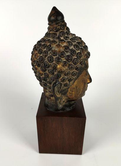 CHINE Belle Tête de Bouddha en bronze ciselé doré à patine brune, les yeux mi-clos...