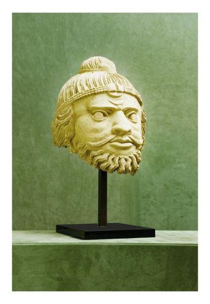 Gandhara 2/4ème siècle. Tête de personnage en stuc, la coiffe ornée d?un ruban et...