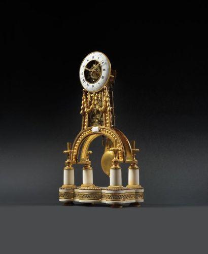 PENDULE SQUELETTE en bronze doré et ciselé, le piétement en arc repose sur une base...