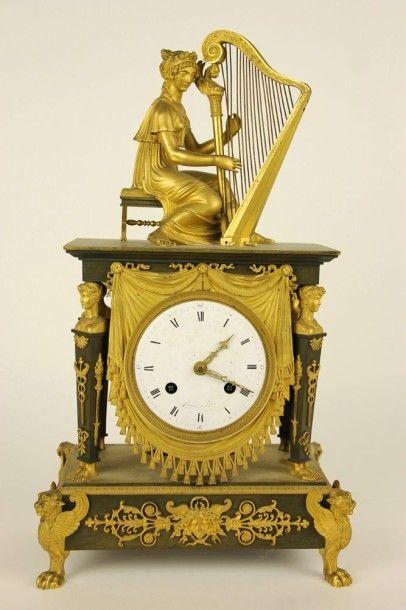 PENDULE en bronze doré et ciselé à double patine figurant la Joueuse de harpe, le...