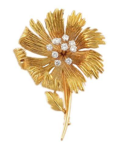 BROCHE en or jaune stylisant une fleur, la...