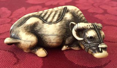 JAPON Netsuke en ivoire sculpté et patiné représentant un buffle couché. Signé sous...