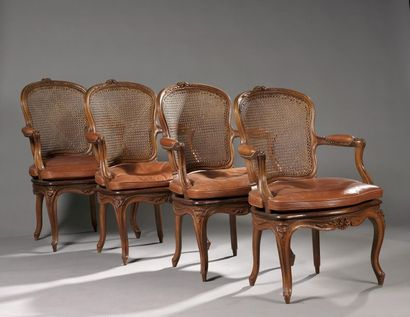 Suite de quatre fauteuils cannés en noyer...