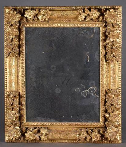 Miroir rectangulaire, l'encarement en bois sculpté et redoré, les angles à décor...