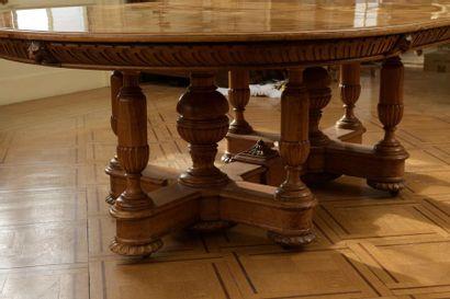 Table de salle à manger en placage de bois clair. Le plateau centré d'une rosace...