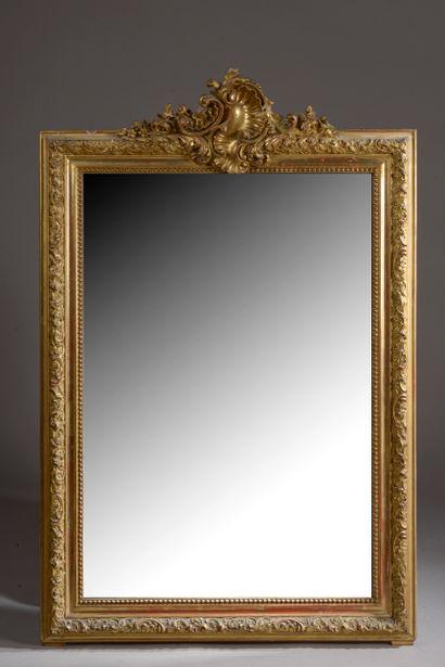 Miroir en bois sculpté et doré ceint d'un...
