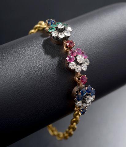 Bracelet en jaune 18k centré de trois fleurs...