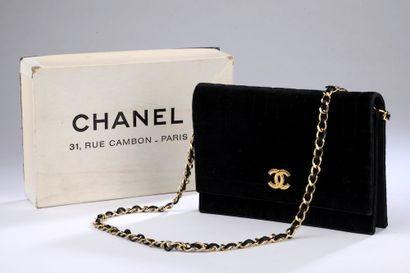 CHANEL.  Quilted black velvet bag with vertical...