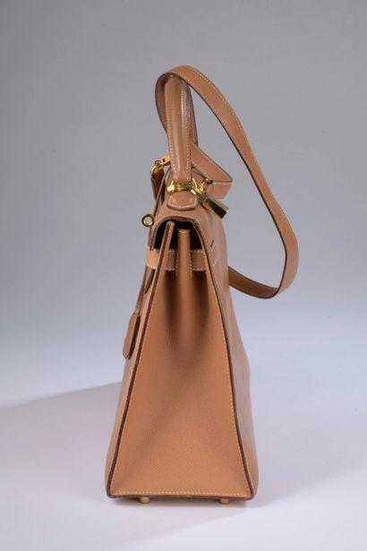 """HERMÈS.  Sac modèle """"Kelly"""" 32 cm en cuir Courchevel gold à surpiqûres sellier blanches,..."""