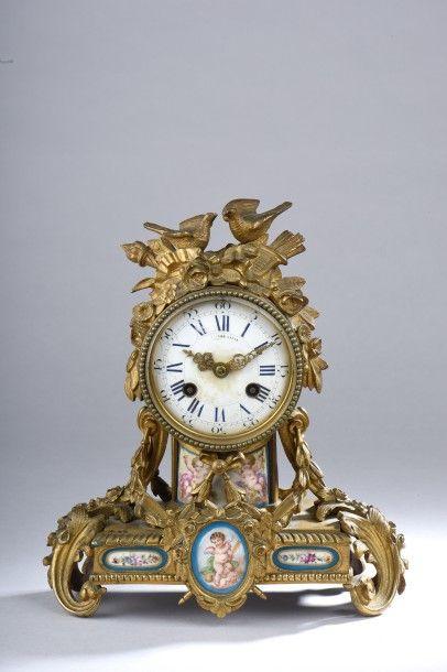 Une horloge en bronze doré à décor de médaillons...