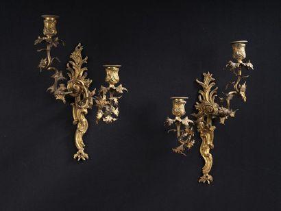 Paire d'appliques en bronze ciselé et doré à deux bras de lumière décalés (manques)....