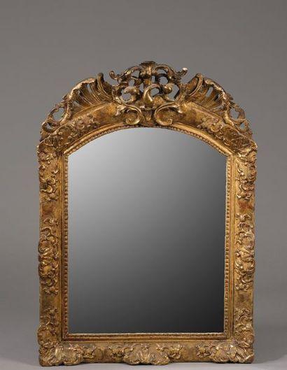 Miroir à fronton légèrement cintré en partie haute en bois et composition redorée....