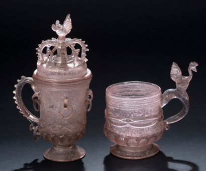 Two pink glass mugs, one covered in blown...
