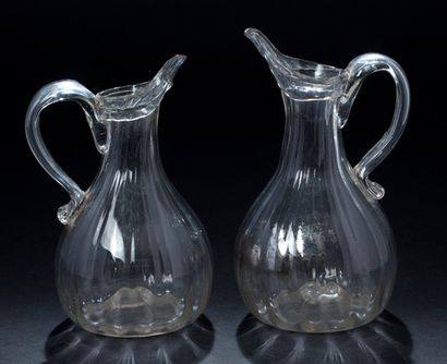 Two clear blown glass cider jugs, of ribbed...